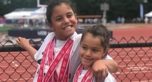 Genesis and Gianna pose with their medals by a fence at the track